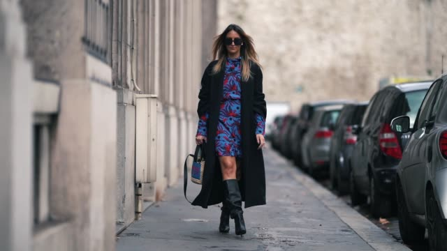 Elisa Taviti wears a dark long coat a blue and red floral print dress black leather high boots a straw basket bag sunglasses outside Rahul Mishra...