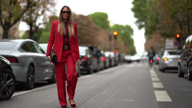 Elisa Taviti wears sunglasses a red blazer jacket a Gucci belt red suit pants outside Valentino during Paris Fashion Week Womenswear Spring/Summer...