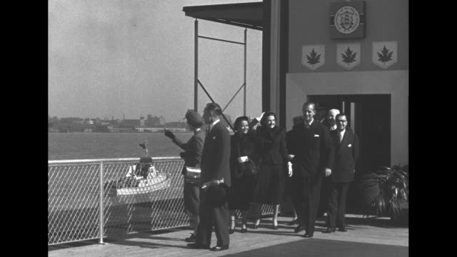 elizabeth and philip on reviewing area overlooking the detroit river / fireboat salute with numerous jets of water / entourage at fence with british... - detroit river stock-videos und b-roll-filmmaterial