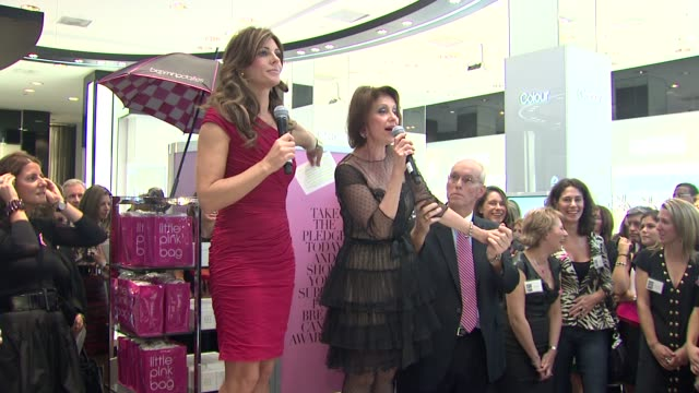 Elizabeth Hurley and Evelyn Lauder encourage the attendees to take a pledge in the pledge booth at the Bloomingdale's The Estee Lauder Companies Kick...
