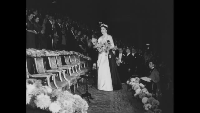 elizabeth ii princess margaret are escorted to seats at empire theatre for the annual motion picture show for the royal family holding bouquets of... - 1952 bildbanksvideor och videomaterial från bakom kulisserna