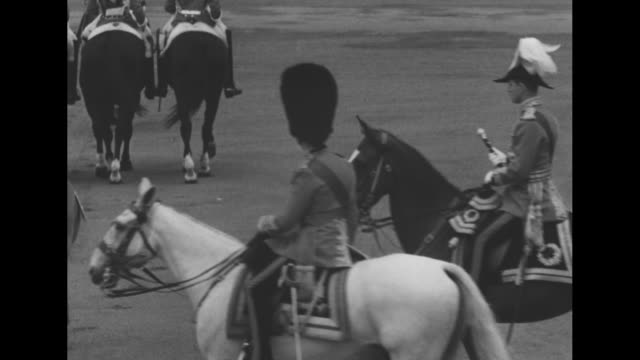 vs elizabeth ii rides sidesaddle on her horse winston around the horse guards parade inspecting the massed grenadier guards followed by husband... - 近衛兵点の映像素材/bロール