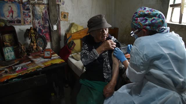 elizabeth romero a nursing assistant, gives a shot of the second dose of the sinovac covid-19 vaccine to dolores mican at her house during a... - latin america stock videos & royalty-free footage