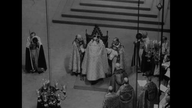 VS Elizabeth seated in King Edward's chair is crowned by Archbishop of Canterbury Geoffrey Fisher who steps away to show Elizabeth with scepter and...