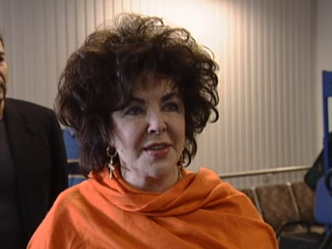 vidéos et rushes de elizabeth taylor poses for photographs and questions at heathrow after arriving on a flight from la to receive her damehood from the queen she said... - châle