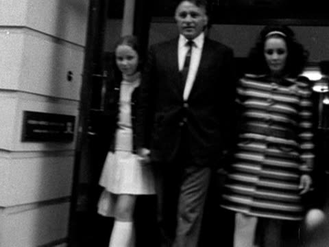 elizabeth taylor richard burton and his daughter kate walk out of a london private hospital to awaiting photographers and journalists. 1968. - actress stock videos & royalty-free footage