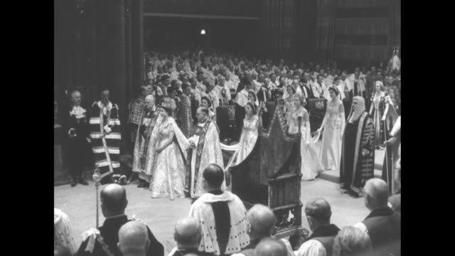 elizabeth, with a very long train, walks to a book followed by 8 maids of honor, walks to a lectern, kneels and bows her head / dean of westminster... - archbishop of canterbury stock videos & royalty-free footage