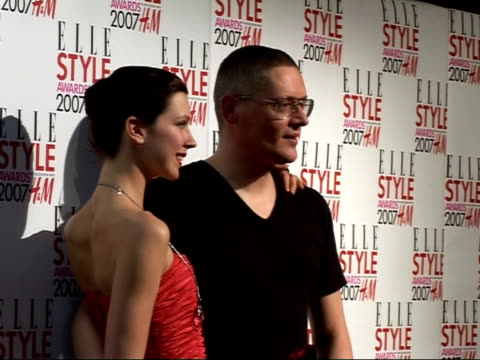 vidéos et rushes de arrivals / interviews giles deacon stands as photographed by press with unidentified woman in red dress - robe rouge