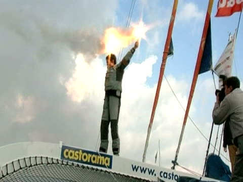 Ellen Macarthur holds two flares as she celebrates successfully breaking the world record for sailing solo around the world nonstop
