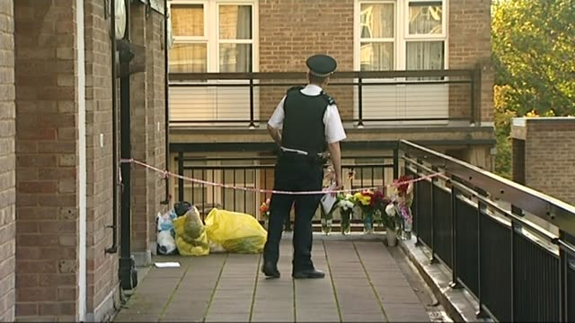 ben butler accuses cps of unfair trial t31101323 / tx england surrey sutton ext police officer outside house floral tributes and cuddly toys on... - 仮設追悼施設点の映像素材/bロール