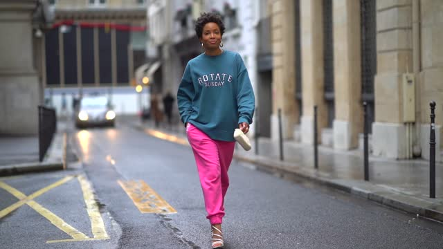 ellie delphine aka slipintostyle wears earrings, a blue oversized wool pullover from rotate, neon pink jogger sport pants from rotate, a small white... - grace stock videos & royalty-free footage