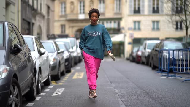ellie delphine aka slipintostyle wears earrings, a blue oversized wool pullover from rotate, neon pink jogger sport pants from rotate, a small white... - short hair stock videos & royalty-free footage