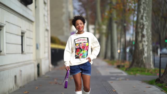 """vidéos et rushes de ellie delphine wears bejeweled long earrings, a white oversized pullover with a printed painting depicting colored flowers and the sentence """"the... - au loin"""