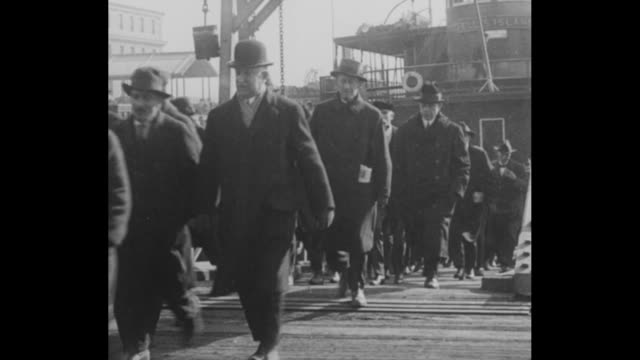 ellis island buildings seen from the water / numerous men walk an incline from boat some covering their faces / the men are seated in a holding room... - comunismo video stock e b–roll