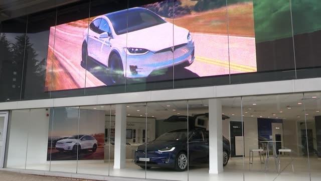 stockvideo's en b-roll-footage met elon musk to step down as chairman of tesla for three years; england: london: ext cars in windows of tesla showroom - itv weekend evening news