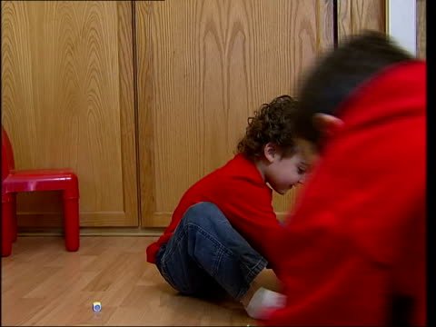 elstree kobi snow playing on floor with other children graphicised seq dr pugh's surgery with inset grainy photograph of dr pugh - grainy stock videos & royalty-free footage