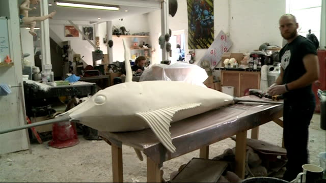elstree studios general views; face masks on wall / people working on masks 'lifecasts' in studio - ボーハムウッド点の映像素材/bロール