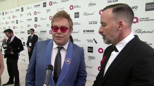 vidéos et rushes de interview elton john and david furnish on hosting the pre oscar party at the 23rd annual elton john aids foundation academy awards viewing party... - oscar party