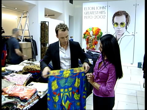 London Nina Nannar standing with David Furnish as Furnish holding up pair of Elton John's trousers which are to be auctioned