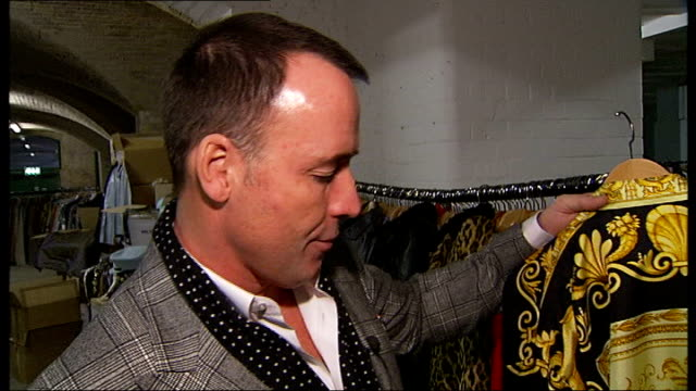 Elton John clothes to be sold in charity auction ENGLAND London INT David Furnish interview with Glen Goodman looking at some of the items on sale...