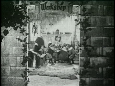 b/w 1925 elves carrying toys in santa's workshop / santa in background - anno 1925 video stock e b–roll