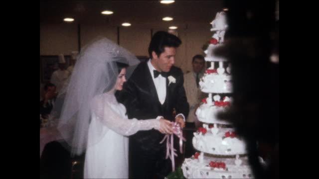 elvis and priscilla cut the wedding cake at their wedding. elvis and priscilla were married on may 1 at the aladdin hotel in las vegas. hdcam-sr at... - プリシラ プレスリー点の映像素材/bロール