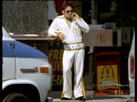 elvis impersonator standing outside burger bar (mcdonalds) smoking, taxis pass in foreground, - doppelgänger stock-videos und b-roll-filmmaterial