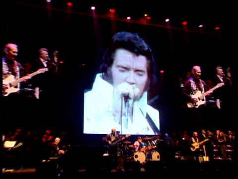comeback/backing band tours england england hampshire bournemouth film recording of elvis presley singing sot on giant screen at concert venue pull... - plucking an instrument stock videos and b-roll footage