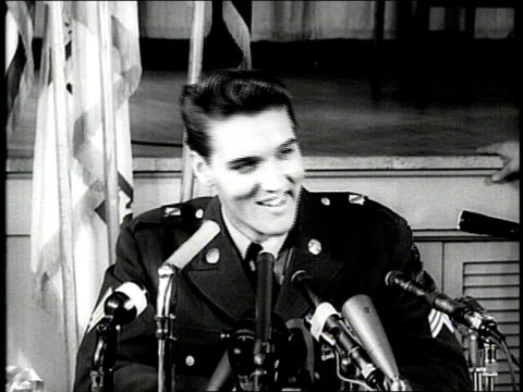 Elvis Presley fields questions from reporters during a press conference