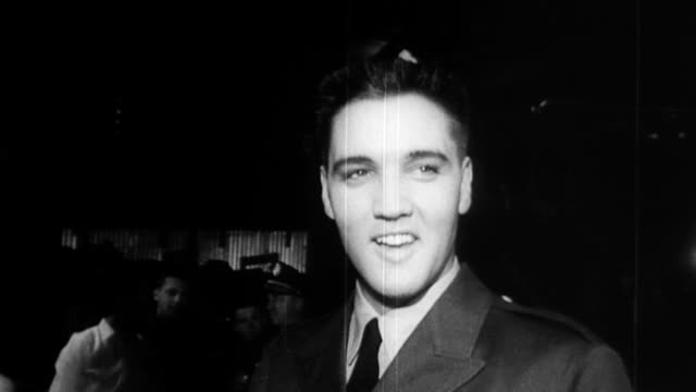 stockvideo's en b-roll-footage met elvis presley in civilian lineup at camp chaffee as joins the army after being drafted / shirtless elvis measured for uniform / elvis tries on... - army