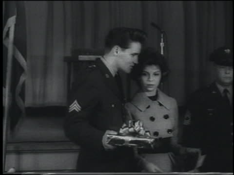 Elvis Presley in his army uniform standing with arm around Nancy Sinatra