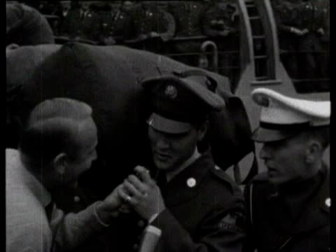 stockvideo's en b-roll-footage met elvis presley walks down gangplank of ship as he arrives in bremerhaven to join his army unit as a truck driver / fans run forward to get a closer... - army