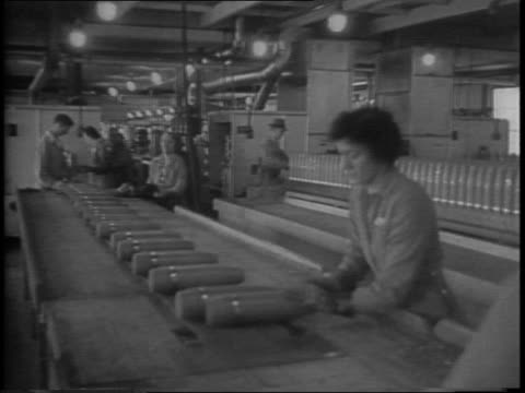 stockvideo's en b-roll-footage met elwood production lines featuring women working on shell cases on an assembly line / women stirring tnt in vats pouring it into casings testing... - munitie