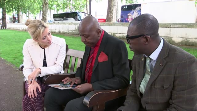 Family speak of anger at lack of witnesses coming forward ENGLAND London EXT Tony Poku and Kofi Baafi chatting to reporter as looking at photograph