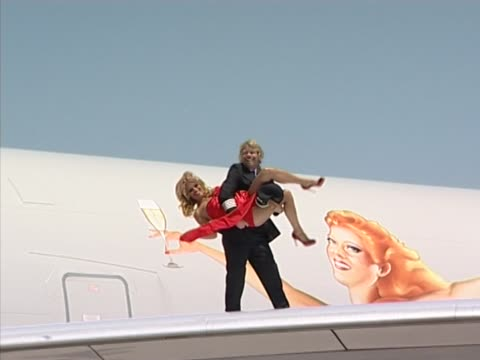 vidéos et rushes de embarrassment for pamela anderson as sir richard branson turns her upside down at the end of a wing walk to celebrate virgin atlantic's 21st... - pin up