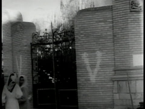 embassy building w/ nazi eagle on top of swastika on railing gate wall w/ allied 'v' painted on bricks british soldiers walking in ruins driving... - nazi swastika stock videos and b-roll footage