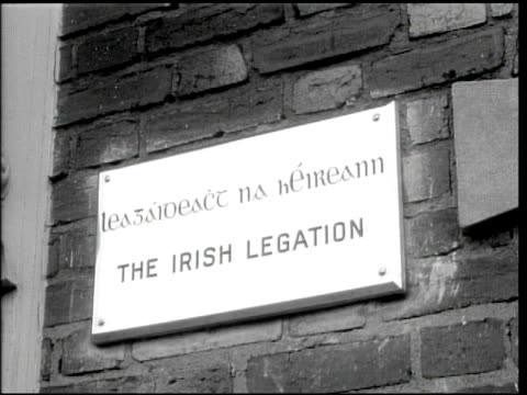 vídeos de stock e filmes b-roll de embassy of ireland w/ flag ms bilingual building plaque 'the irish legation' irish ambassador robert brennon sitting at desk talking working w/... - 1944