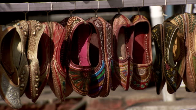 Embellished shoes hang from a rack at a market. Available in HD
