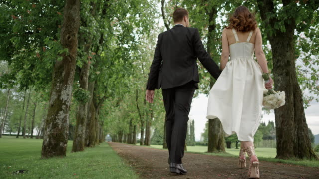 slo mo ds embraced bride and groom walking down the avenue - wedding dress stock videos & royalty-free footage