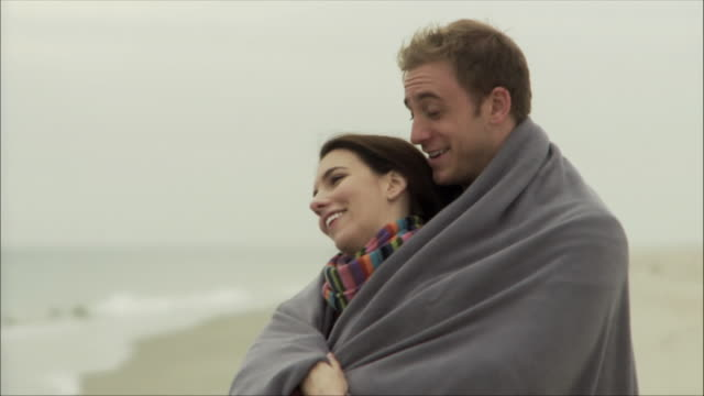 MS Embracing couple wrapped in blanket looking at sea / Sea Bright, New Jersey, USA