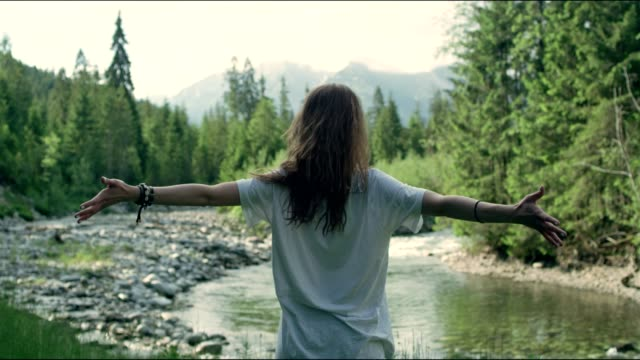 Embracing nature - woman enjoying view with opened arms