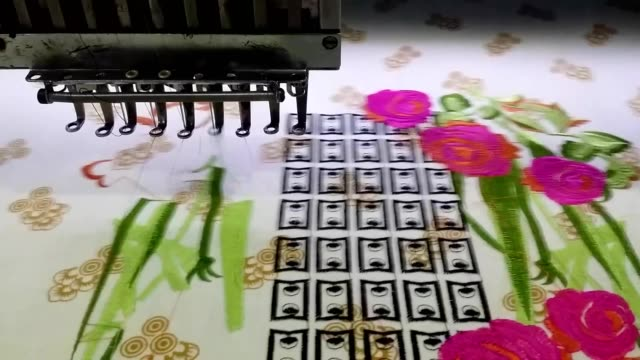 embroidery machine doing automatic embroidery on fabric - embroidery stock videos & royalty-free footage