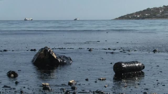 vídeos de stock, filmes e b-roll de emergency crews were scrambling tuesday to contain an oil spill near athens after an old tanker sank close to salamis island over the weekend - vazamento de óleo