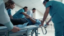 Emergency Department: Doctors, Nurses and Paramedics Run and Push Gurney / Stretcher with Seriously Injured Patient towards the Operating Room. Bright Modern Hospital with Professional Staff Saving Lives.