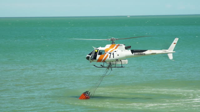 emergency fire fighting helicopter collecting water from the sea - rescue worker stock videos and b-roll footage