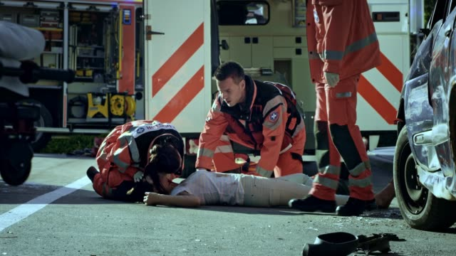 emergency medical service team checking the vital signs of a young woman lying on the ground at the scene of a car crash - traffic accident stock videos & royalty-free footage
