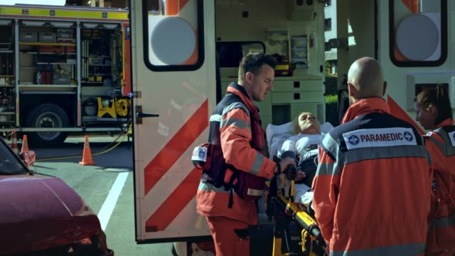 emergency medical service team loading an injured person on the stretcher into the ambulance - rescue worker stock videos & royalty-free footage