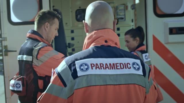 Ärztlicher Notdienst Team laden eine verletzte junge Frau in den Krankenwagen halten Sie ihre Sauerstoff-Maske