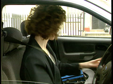 Emergency mobile phone system for female motorists ENGLAND London CMS SIDE woman in car as trying to start car as opens bag taking out phone CS...