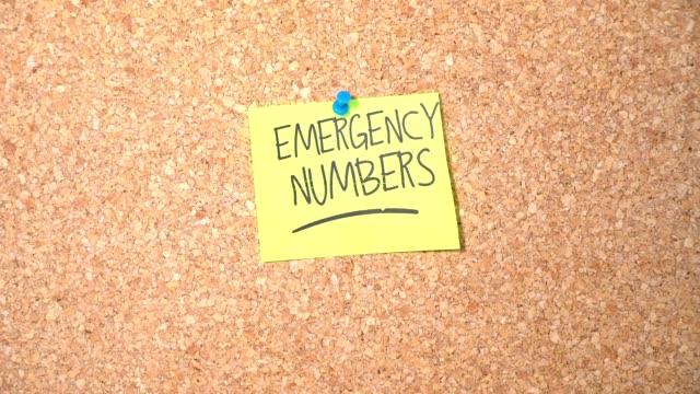 notfall-nummern wortgruppe auf papier fixieren sich auf pinnwand von einem mann - feuerwehr hinweisschild stock-videos und b-roll-filmmaterial